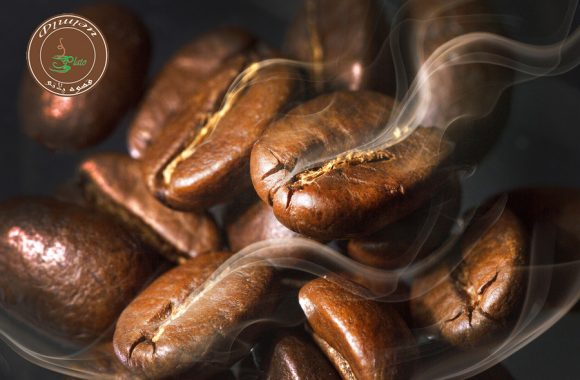 Roasted coffee beans. Seeds of freshly roasted coffee with smoke. Coffee beans closeup with emphasis on the grain with smoke.